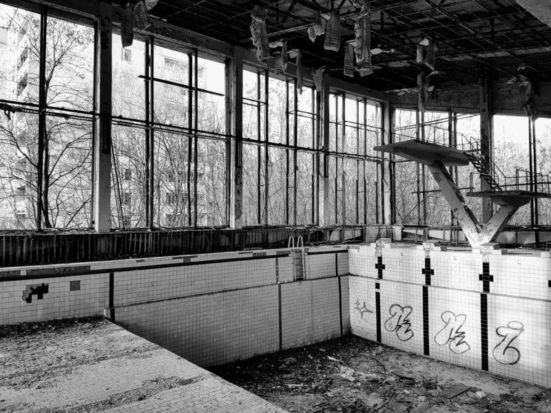 black and white photo of abandoned swimming pool in Pripyat, Chernobyl